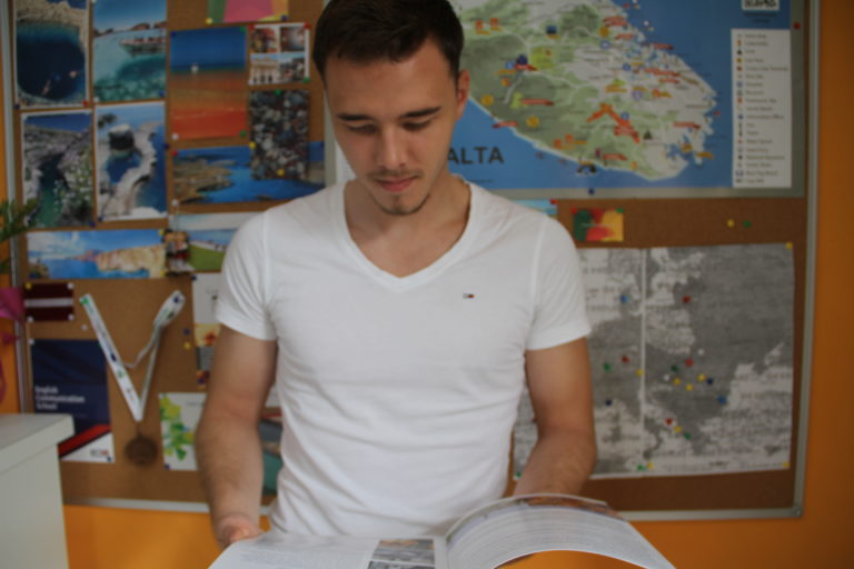 Man indoors at school with is computer for Erasmus
